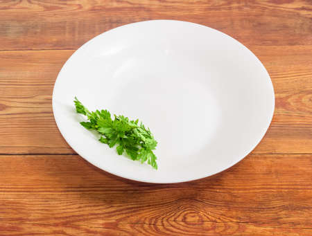 potherb: Background of a white dish with bunch of fresh parsley on the edge of a dish on an old wooden surface
