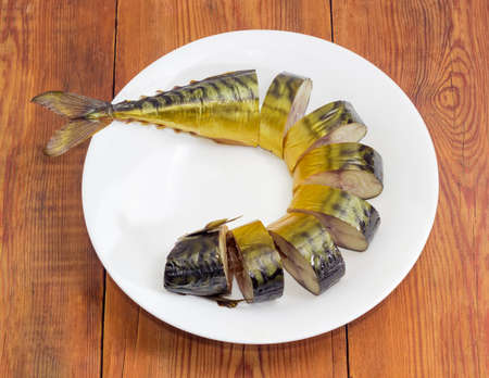 kipper: Sliced cold-smoked Atlantic mackerel on a white dish on an old wooden surface  Stock Photo