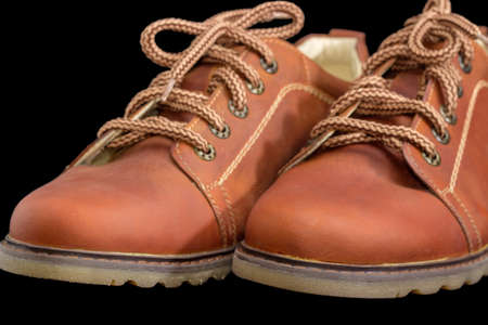 Toes of new leather brown mens shoe  with a shoelaces and eyelets on a dark background closeup  Stock Photo