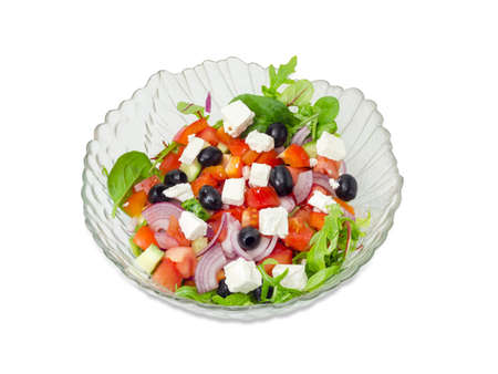 ensalada tomate: Greek salad in a glass salad bowl on a white background.