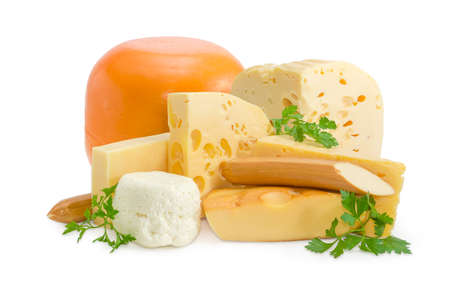 Several different pieces of semi-hard cheese and soft cheese various types and twigs of parsley on a light background