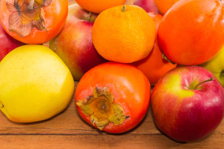 Pile of ripe fresh persimmons, apples and mandarin oranges on an old wooden surface closeup