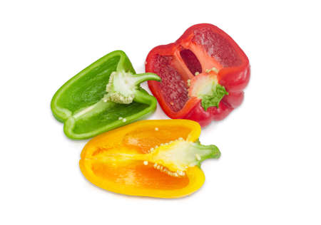 insides: Green, yellow and red fresh bell peppers, cut in half on a light background