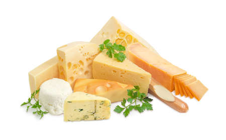 Several different pieces of hard cheese, semi-hard cheese and soft cheese various types and twigs of parsley on a light background