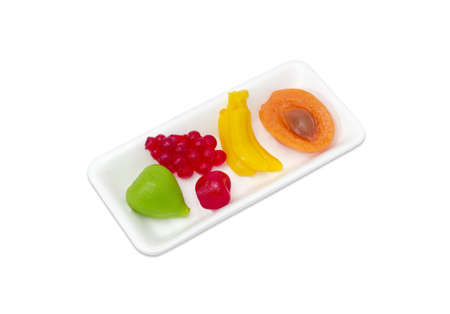 pectin: Several jelly candies gelatin based in the shape of different fruits in a small plastic tray on a light background