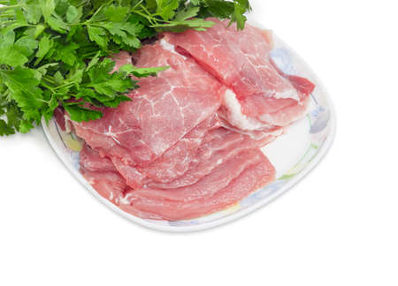 Sliced fresh chilled pork on a dish closeup against the background of bunch of parsley on a light background