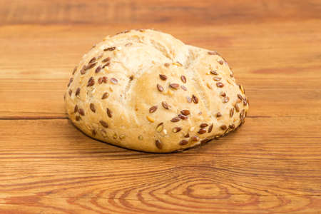 Round wheat sourdough bun, sprinkled with flax and sesame seeds on an old wooden surface  Stock Photo
