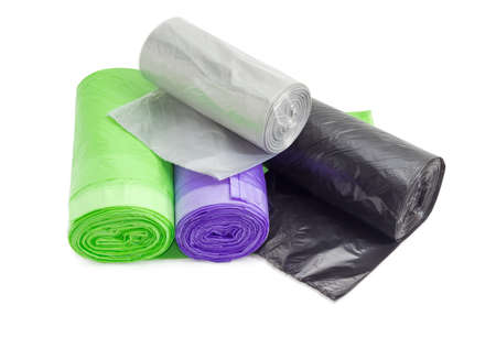Several plastic disposable garbage bags of different sizes and colors in rolls including biodegradable on a light background Standard-Bild