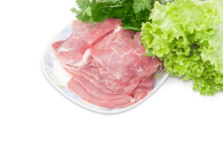 Sliced fresh chilled pork on a dish closeup against the background of bunch of parsley and lettuce on a light background