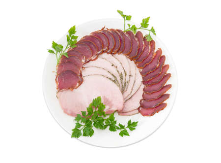 charcutería: Sliced dried pork tenderloin and ham with twigs of parsley on a white dish on a light background
