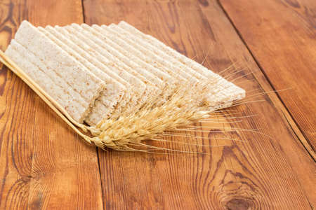 Several dietary wheat wholegrain crispbread with adding a buckwheat and a barley and two wheat spikes closeup on a surface of an old wooden planks  Stock Photo