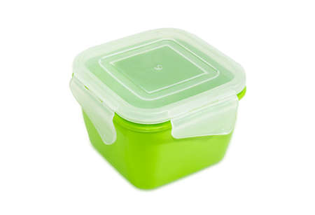 Green reusable plastic food storage container with translucent cover for home use on a light background  Stock Photo
