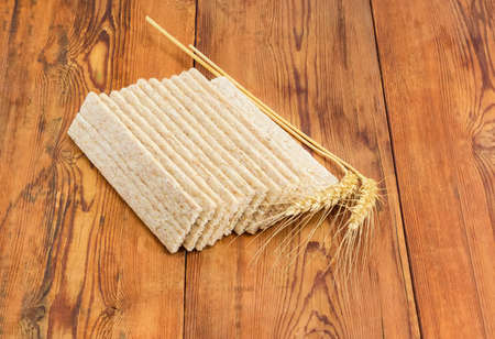 Dietary wheat wholegrain crispbread with adding a buckwheat and a barley and two wheat spikes on a surface of an old wooden planks  Stock Photo