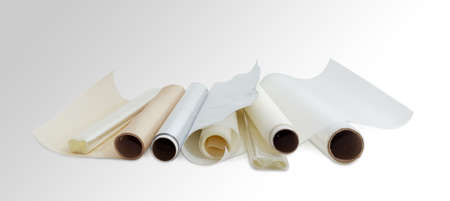 Several rolls of the plastic oven bags, plastic food wrap, aluminum foil and various parchment paper for household use on a light background.