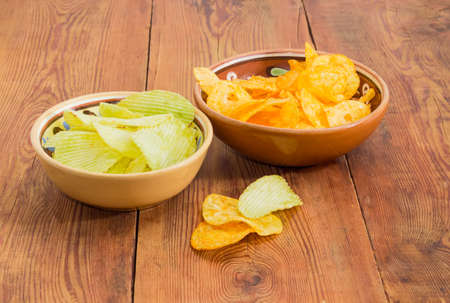 Potato chip flavored wasabi and paprika in two different ceramic bowls on an old wooden surface