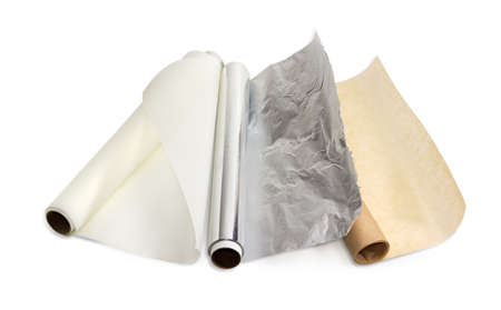 Two rolls of the various parchment paper and one roll of the aluminum foil for household use on a light background.