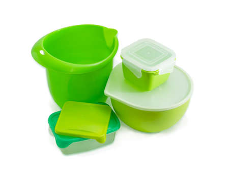 Several different green reusable plastic food storage and cooking containers, some with covers, for home use on a light background