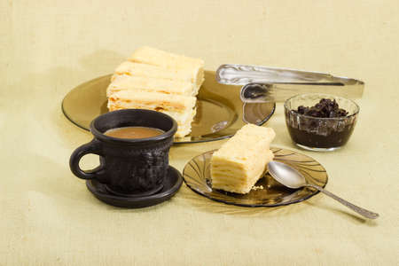 One piece of layered sponge cake on a glass saucer with spoon, several pieces of cake on glass dish, coffee with milk in black cup and jam on a cloth surface