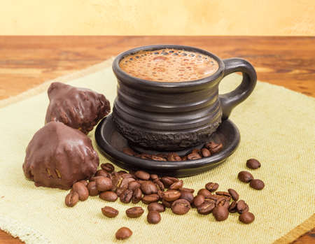 Freshly brewed coffee latte in a black ceramic cup, roasted coffee beans and two chocolate truffles on a napkin on a wooden surface  Stock Photo