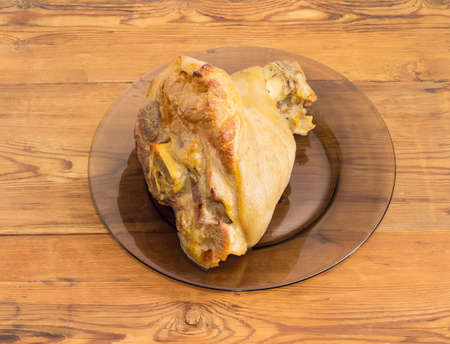 Baked ham hock on a glass dish on a surface of old wooden planks  Stock Photo