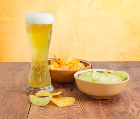 Beer glassware with the lager beer, two different kinds of the potato chip flavored paprika and wasabi in ceramic bowls on an old wooden table on a background of an yellow wall