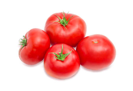 Several ripe red tomatoes closeup on a light background