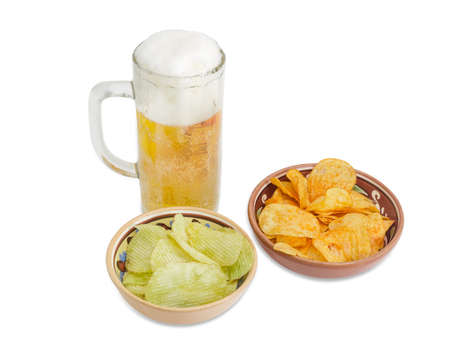 Beer glassware with lager beer, potato chip flavored paprika and wasabi in two different ceramic bowls on a light background
