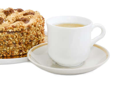 White cup with coffee with cream on a background of sponge cake, decorated with butter cream and sprinkled with grated nuts on a light background  Stock Photo