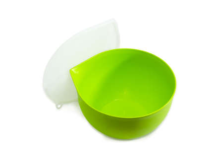 Green reusable plastic round food storage and cooking container for home use with open translucent cover on a light background