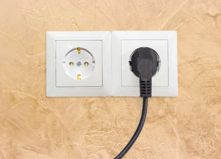 ac: Block of the two white socket outlets European standard with connected one black power cable with corresponding AC power plug closeup on a yellow wall