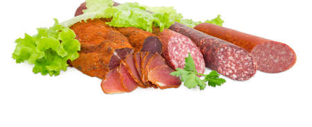 Partly sliced pieces of the dried pork tenderloin and the different cooked smoked and dry smoked sausages with greens closeup on a light background