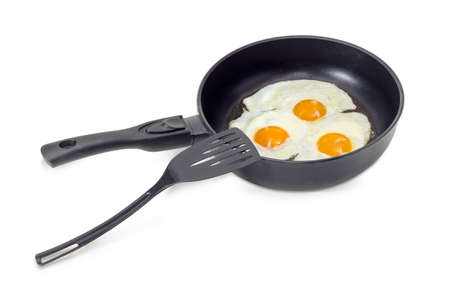 Three freshly fried eggs prepared with unbroken yolk in the frying pan and the black plastic spatula on a light background  Reklamní fotografie