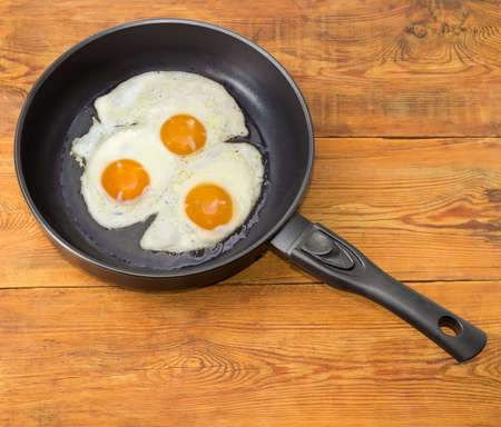 Three freshly fried eggs prepared with unbroken yolk in the frying pan on a surface of an old wooden planks  Stock Photo