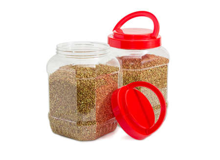 Buckwheat groats peeled from the husk in two transparent plastic containers with the red covers, one of them open on a light background  Stock Photo