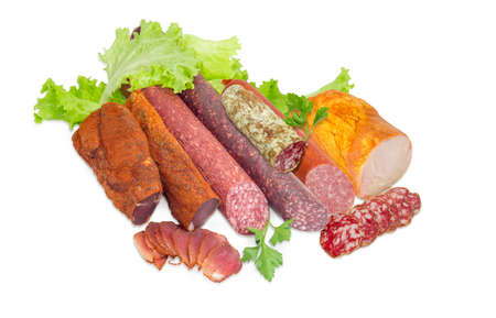 Partly sliced two pieces of the dried pork tenderloin, different varieties of cooked smoked and dry smoked sausages, salami, ham with turkeys, parsley and lettuce on a light background