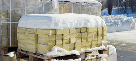 Yellow decorative face bricks covered snow on the wooden pallet against the background of other pallets with bricks on an outdoor warehouse in winter sunny day