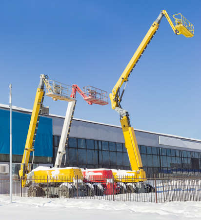 inaccessible: The three different self propelled wheeled hydraulic articulated boom lift with telescoping booms and baskets against the sky and the industrial building in winter sunny day
