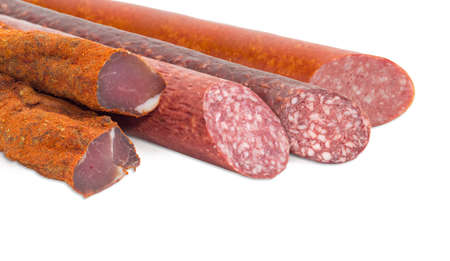 Fragment of the partly sliced pieces of the dried pork tenderloin and the different cooked smoked and dry smoked sausages closeup on a light background