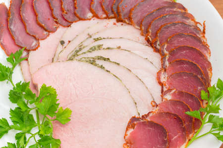 Fragment of white dish with sliced dried pork tenderloin, ham and twigs of parsley closeup