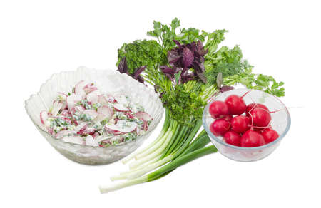 potherb: Salad of the sliced red radish, green onion with sour cream in the glass salad bowl and separately whole red radish in glass bowl, bundle of the green onion and greens on a light background  Stock Photo