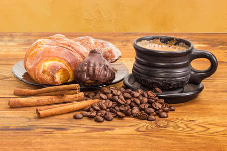 Freshly brewed coffee with milk in the black ceramic cup, scattered beside roasted coffee beans and cinnamon sticks, chocolate truffle and croissant on the glass saucer on the old wooden surface  Stock Photo