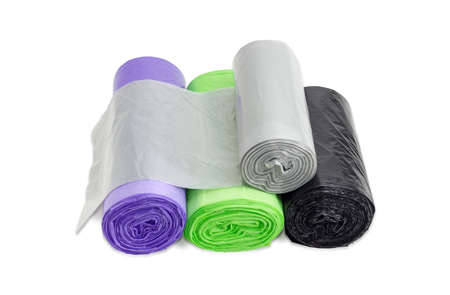 Diverse borse per la spazzatura di plastica monouso di diverse dimensioni e colori in rotoli, tra cui biodegradabili e con manici che possono essere legati su uno sfondo chiaro