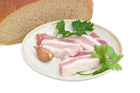 Several slices of uncooked streaky pork belly bacon, garlic, twigs of parsley and cilantro on saucer against the background of cut hearth brown bread closeup on a light background Stock Photo