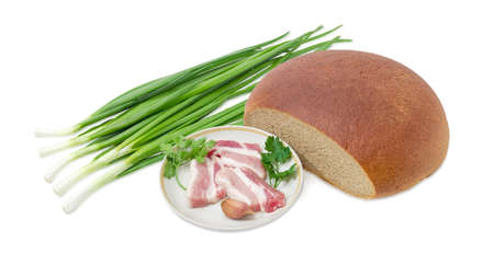 Several slices of uncooked streaky pork belly bacon, garlic, twigs of parsley and cilantro on dish,  partly incised hearth wheat and rye bread,  stalks of green onion on a light background
