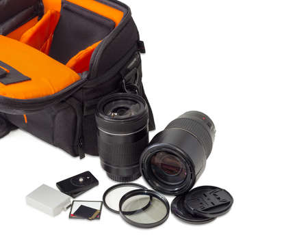 Two different photo lenses and some other photo accessories against the background of the fragment of the open camera bag on a light background Stock Photo