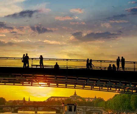 View from a river to silhouettes of the people on the bridge, other bridge on the river Seine and Great Palace in Paris in the rays of the setting sun Standard-Bild