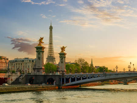 View from the river Seine of part of the Bridge of Alexander III and Eiffel Tower in Paris in the rays of the setting sun