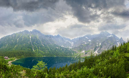 View from above of the mountain lake with coasts overgrown with the forest on the background of the craggy mountain slopes and sky with storm clouds Stock Photo