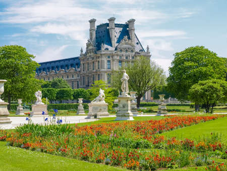 Corner of the Tuileries Garden with flower bed and alley with sculptures in Paris in springtime