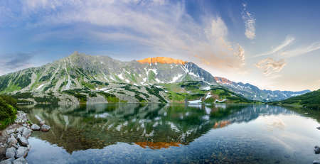 Panorama of the mountain lake with coasts overgrown with grass and mountain pine and the craggy slope of the mountain gorge reflected in water on the sunset Stock Photo